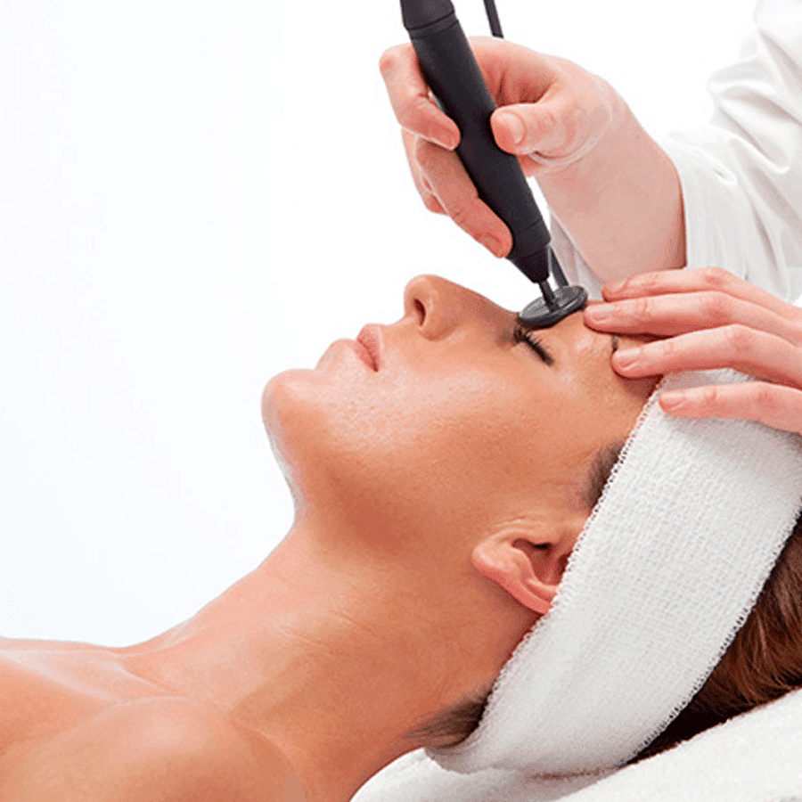 Diatermia Facial. Mujer aplicándose tratamiento con aparatología. Centro de estética y belleza en Terrassa