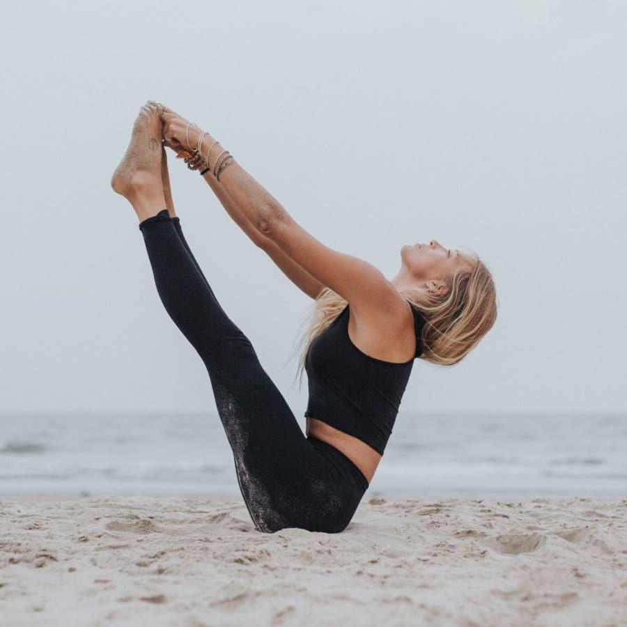Los beneficios del yoga para cuerpo y mente. Mujer haciendo yoga en la playa